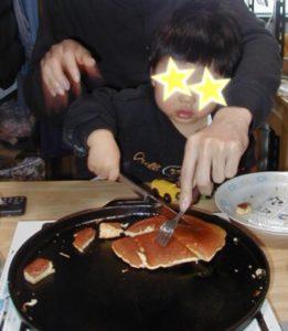 鉄板の上のホットケーキをバターナイフて切っている2歳児